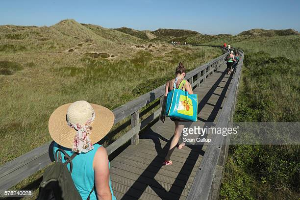Visitors walk along a wooden walkway across protected sand dunes after a day at the beach on Sylt Island on July 19 2016 near Wenningstedt Germany...