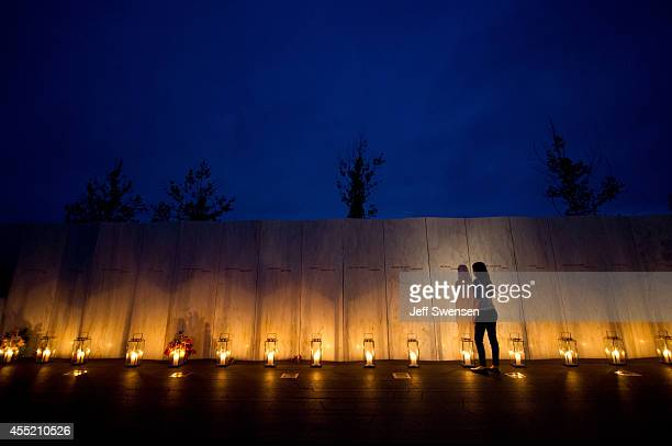 Visitors walk along the wall of names of passengers who perished in the 9/11 terrorist attacks on the eve of the 13th anniversary of the attacks at...