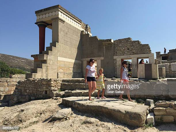 Visitors walk among partiallyreconstructed ruins of the ancient Minoan city of Knossos on the island of Crete on August 22 2015 in Knossos Greece...