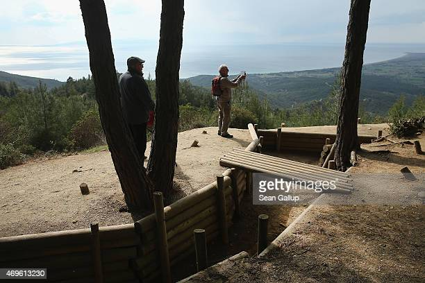 Visitors walk among recreated Turkish trenches from the Gallipoli campaign at Chunuk Bair as the Aegean Sea lies behind on April 8 2015 near Eceabat...