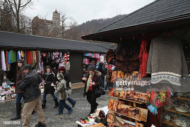 Visitors walk among souvenir shops backdropped by Bran Castle famous as 'Dracula's Castle' on March 10 2013 in Bran Romania Bran Castle's reputation...
