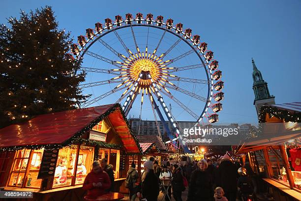 Visitors walk among stalls selling mulled wine at the annual Christmas market at Alexanderplatz as a ferris wheel stands behind on November 24 2015...