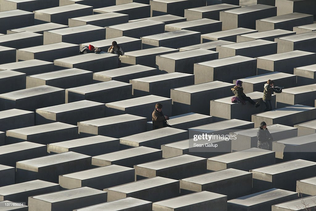 Visitors walk among stellae at the Memorial to the Murdered Jews of Europe also called the Holocaust Memorial on January 26 2012 in Berlin Germany...
