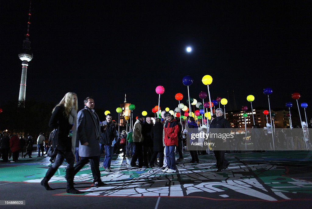 Visitors walk amongst large illuminated pins stuck into a painted 1:775 scale map of Berlin in front of the Fernsehturm (Television Tower) during celebrations marking the 775th anniversary of the city of Berlin on October 28, 2012 in Berlin, Germany. The settlement of Coelln, which stood opposite Berlin on the Spree river, is first referred to in a document from 1237, and by the beginning of the 14th century Coelln and Berlin joined together to become the region's most important trading center.