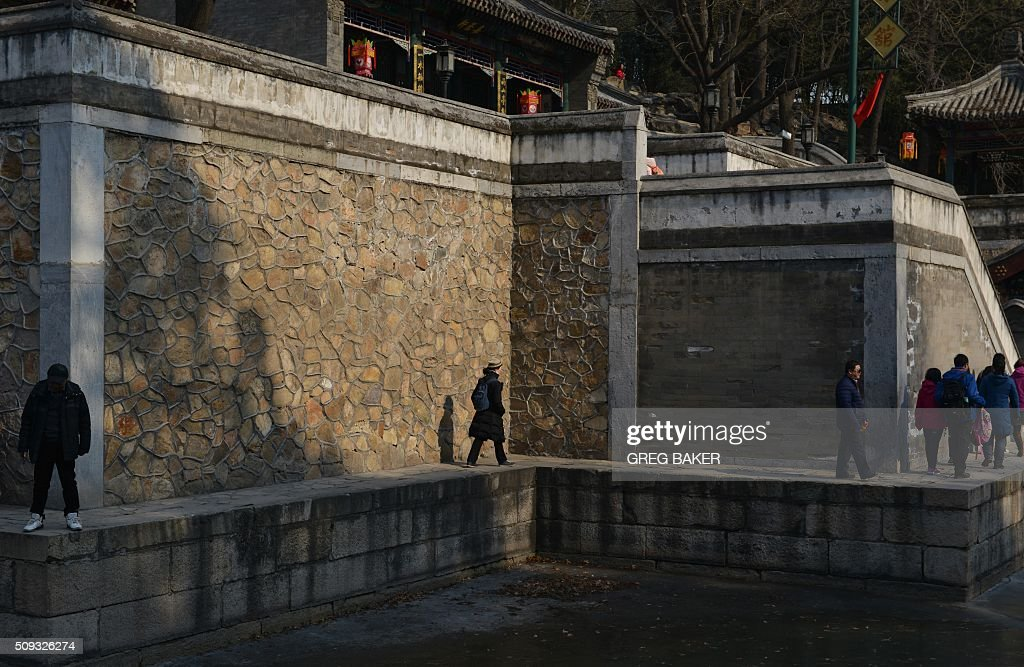 Visitors walk around a frozen lake at the Summer Palace during Lunar New Year celebrations in Beijing on February 10, 2016. Millions of Chinese are celebrating the 'Spring Festival', the most important holiday on the Chinese calendar, which this year marks the beginning of the Year of the Monkey. AFP PHOTO / GREG BAKER / AFP / GREG BAKER