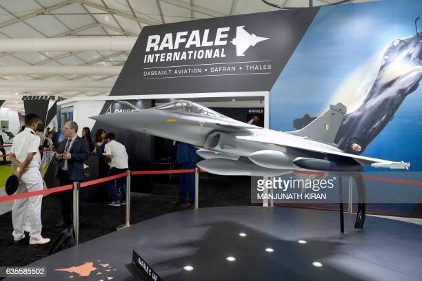 Visitors walk around a scaled down model of Grippen E fighter at the Dassault aviation stall on the third day of the 11th edition of 'Aero India' a...