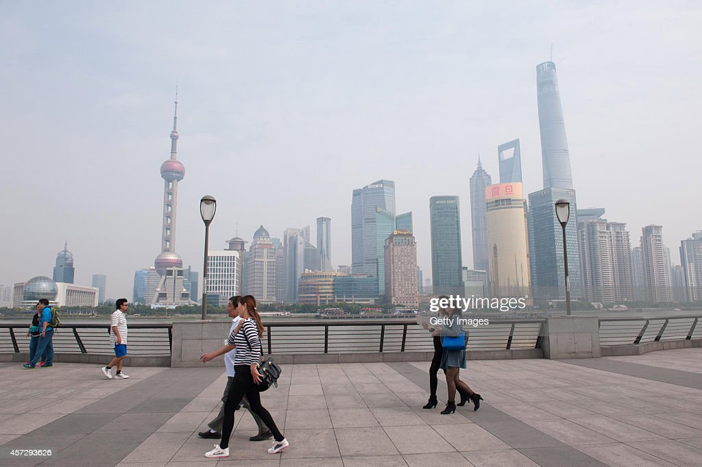 Visitors walk around in smog at The Bund on October 16 2014 in Shanghai China A report from Shanghai Environmental Monitoring Center said that the...