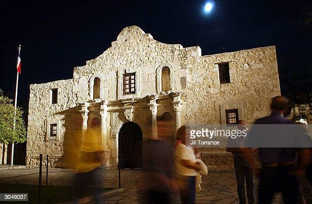 Visitors walk around outside of the Alamo the night before the 168th Anniversary of the 1836 Fall of the Alamo March 5 2004 in San Antonio Texas The...