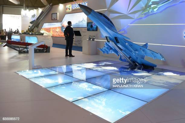 Visitors walk around scaled down models of aircraft at the Dassault on the third day of the 11th edition of 'Aero India' a biennial international...