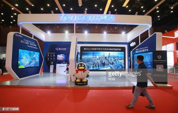 Visitors walk around Tencent booth at the 16th China Internet Conference is pictured at China National Convention Center on July 12 2017 in Beijing...