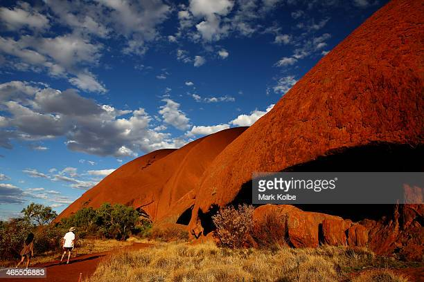 Visitors walk around the base of Uluru on the base walk trail on November 27 2013 in UluruKata Tjuta National Park Australia Uluru/ Ayers Rock is a...