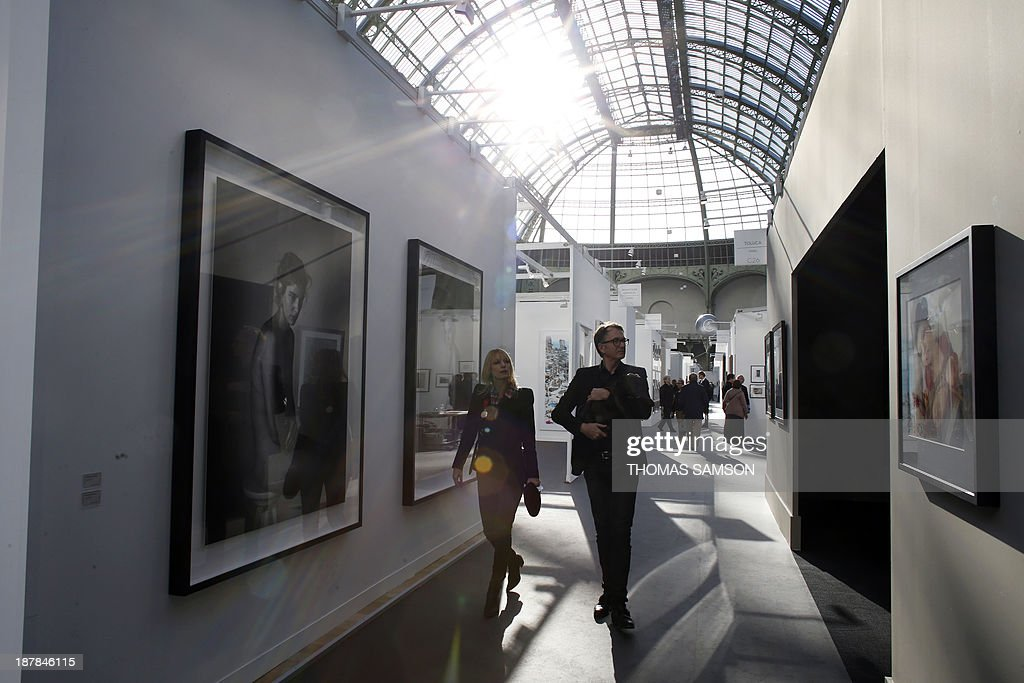 Visitors walk around the exhibition space during the 17th edition of the Paris Photo photography fair, on November 13, 2013, in Paris. The Paris Photo fair is taking place at the Grand Palais from November 14 to 17. AFP PHOTO / THOMAS SAMSON