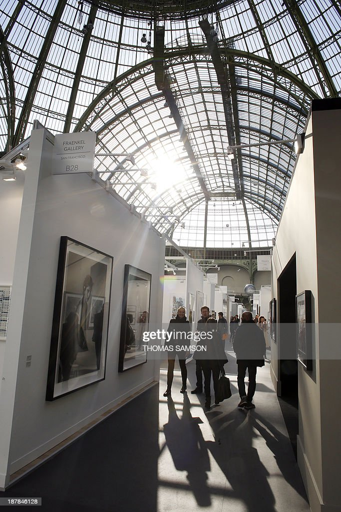 Visitors walk around the exhibition space during the 17th edition of the Paris Photo photography fair, on November 13, 2013, in Paris. The Paris Photo fair is taking place at the Grand Palais from November 14 to 17.