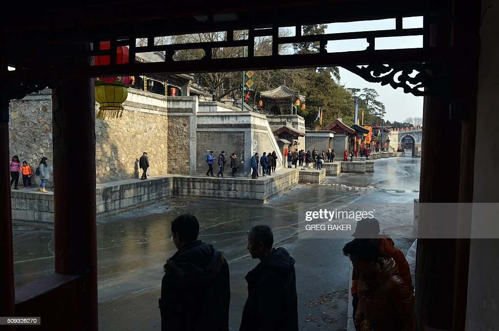 Visitors walk beside a frozen lake at the Summer Palace during Lunar New Year celebrations in Beijing on February 10, 2016. Millions of Chinese are celebrating the 'Spring Festival', the most important holiday on the Chinese calendar, which this year marks the beginning of the Year of the Monkey. AFP PHOTO / GREG BAKER / AFP / GREG BAKER