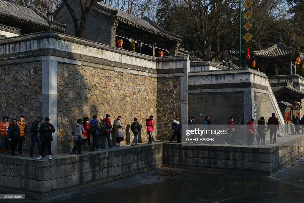 Visitors walk beside a frozen lake at the Summer Palace during Lunar New Year celebrations in Beijing on February 10, 2016. The Summer Palace was the summer retreat of China's emperors on the outskirts of the Chinese capital. Millions of Chinese are celebrating the 'Spring Festival', the most important holiday on the Chinese calendar, which this year marks the beginning of the Year of the Monkey. AFP PHOTO / GREG BAKER / AFP / GREG BAKER