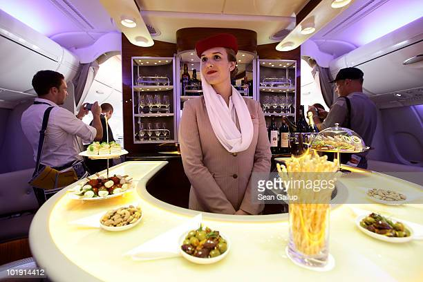 Visitors walk by a stewardess at the bar in the first class section of an Emirates Airbus A380 at the ILA Berlin Air Show on June 9 2010 in Berlin...