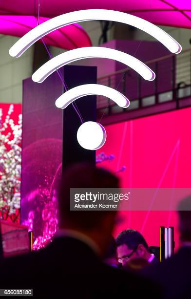 Visitors walk by a Wireless Zone sign at the Telekom stand at the CeBIT 2017 Technology Trade Fair on March 21 2017 in Hanover Germany The 2017 CeBIT...