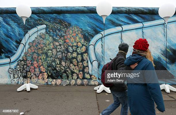 Visitors walk by East Side Gallery a section of the former Berlin Wall during celebrations for the 25th anniversary of the fall of the Wall on...