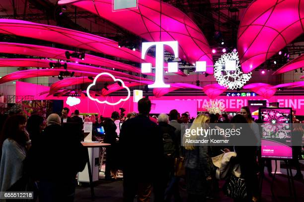 Visitors walk by the Telekom stand at the CeBIT 2017 Technology Trade Fair on March 20 2017 in Hanover Germany The 2017 CeBIT will run from March 2024
