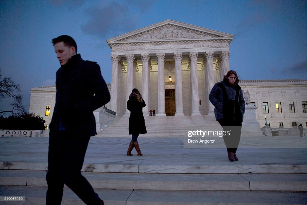 Visitors walk by the U.S. Supreme Court is seen at dusk February 13, 2016 in Washington, DC. Supreme Court Justice Antonin Scalia was at a Texas Ranch Saturday morning when he died at the age of 79.