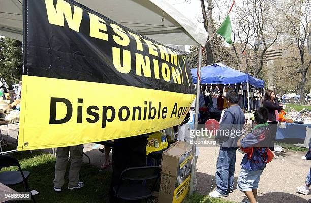 Visitors walk by the Western Union booth at Denver's Cinco de Mayo festival May 8 2005 First Data's Western Union unit and many other firms seeking...