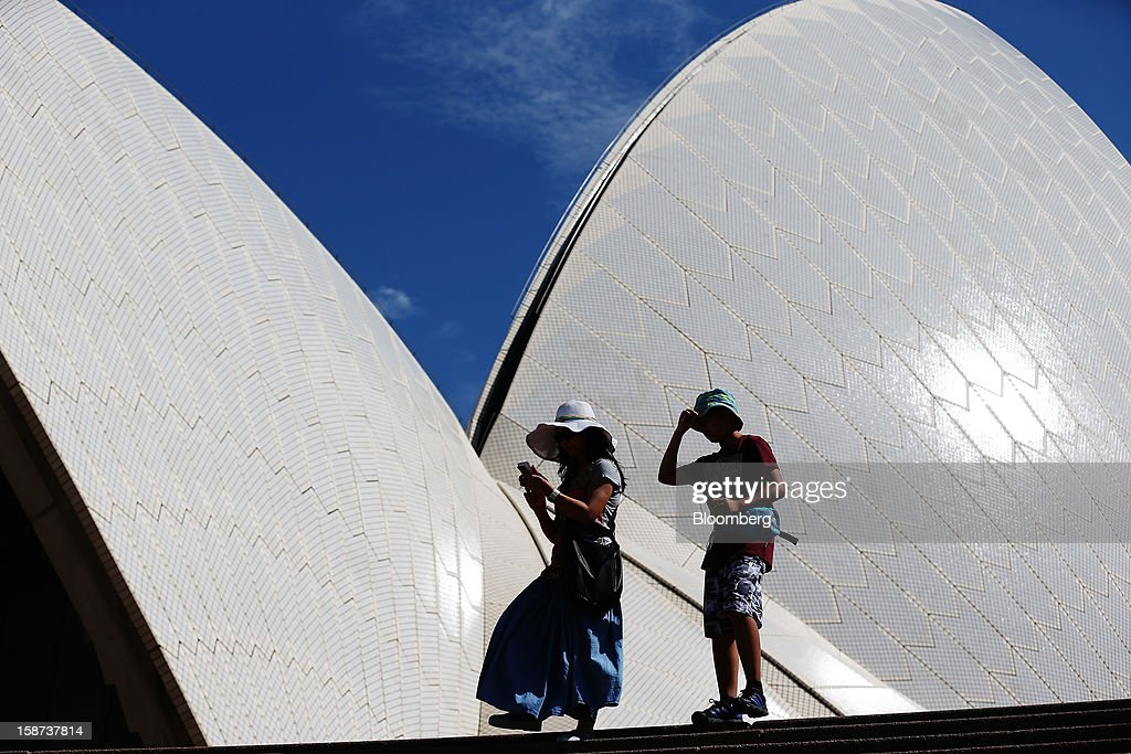 Visitors walk down a set of steps in front of the Sydney Opera House in Sydney, Australia, on Monday, Dec. 24, 2012. At least 150,000 people from mainland China and across Asia are projected to descend on Sydney, Australia's most populous city, during the New Year's Eve and Chinese New Year period. Photographer: Brendon Thorne/Bloomberg via Getty Images