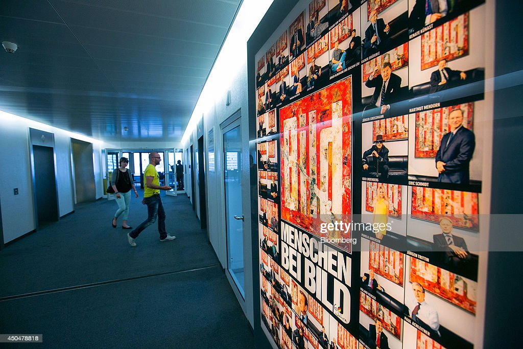 Visitors walk in a corridor as an advertisement for tabloid newspaper Bild, published by Axel Springer SE, stands illuminated inside the company's offices in Berlin, Germany, on Wednesday, June 11, 2014. Axel Springer, Europe's biggest newspaper publisher, is working with JPMorgan Chase & Co. and Citigroup Inc. on an initial public offering of its digital-classifieds business, people familiar with the matter said. Photographer: Krisztian Bocsi/Bloomberg via Getty Images
