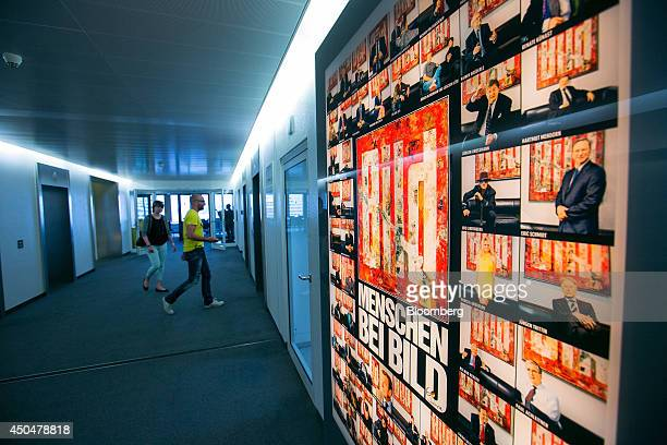 Visitors walk in a corridor as an advertisement for tabloid newspaper Bild published by Axel Springer SE stands illuminated inside the company's...