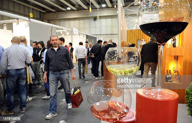 Visitors walk in an alley on March 25 2012 at the Vinitaly exposition in Verona The 46th international wine and spirits exhibition Vinitaly will run...