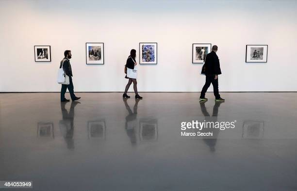 Visitors walk in front of some of the photographs by Irving Penn during the press preview of the new exhibition at Palazzo Grassi on April 11 2014 in...