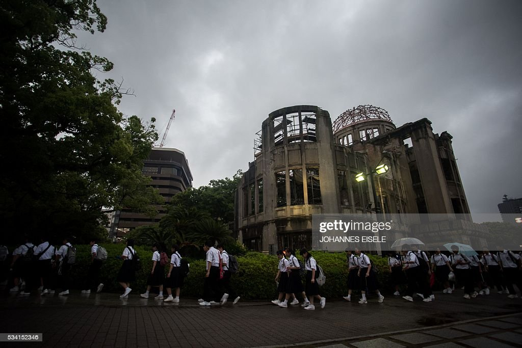 Visitors walk in front of the Peace Memorial Genbaku Dome in the Hiroshima Peace Memorial park in Naka Ward, Hiroshima Prefecture on May 25, 2016. US President Barack Obama is set to become the first sitting US president to visit Hiroshima when he journeys on May 27 with Japanese Prime Minister Shinzo Abe, hallowed ground to Japanese but, for more than 70 years, a no-go zone for 11 of his Oval Office predecessors. / AFP / JOHANNES