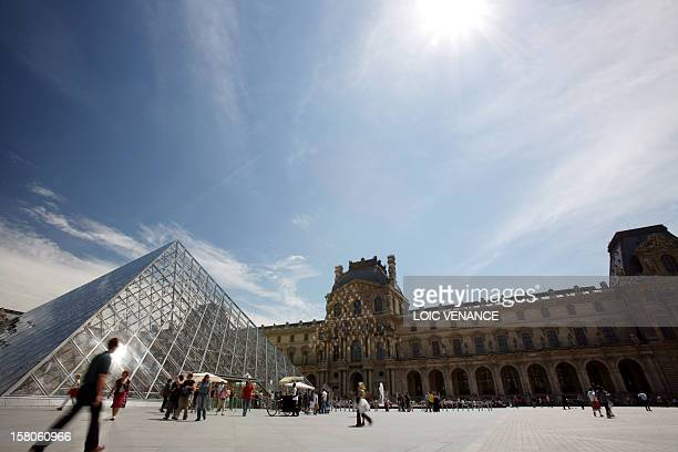 Visitors walk in front of the Pyramid the entrance of the Louvre Museum on June 17 2009 in Paris AFP PHOTO LOIC VENANCE