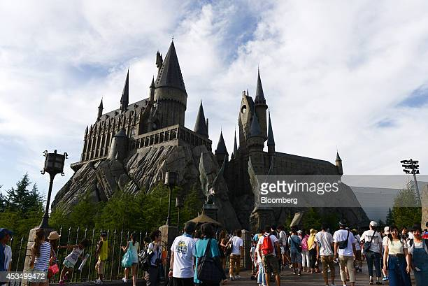 Visitors walk in front of The Wizarding World of Harry Potter themed area at Universal Studios Japan operated by USJ Co in Osaka Japan on Thursday...