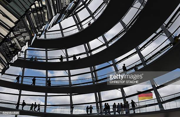 Visitors walk in the glass cupola of the Reichstag building hosting the German parliament in Berlin Germany on June 10 2016 / AFP / CHRISTOF STACHE