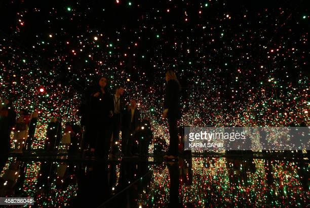 Visitors walk inside an art installation by Yayoi Kusama titled 'Infinity Mirrored Room Filled with the Brilliance of Life' at a preopening...