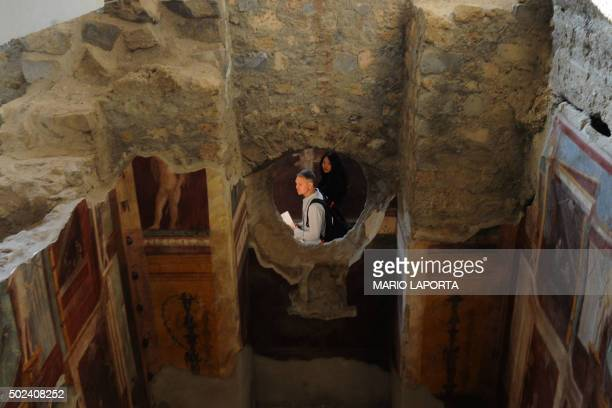 Visitors walk inside the Criptoporticus Domus one of six restored domus at UN World Heritage Site Pompeii on December 24 2015 during the official...