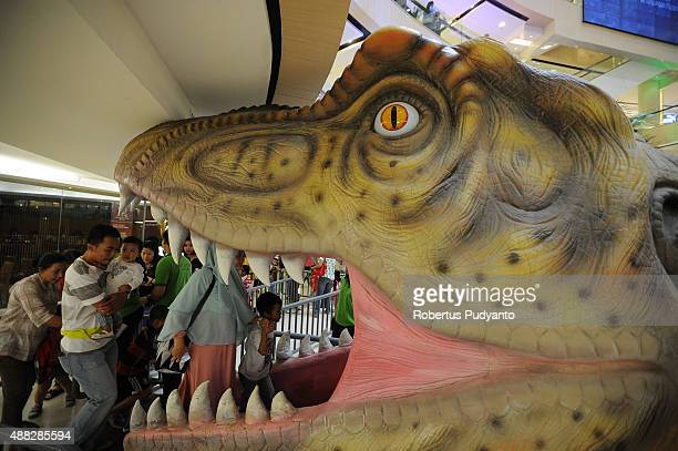 Visitors walk into Dinosaur Adventure and Learning Experience Park at Tunjungan Plaza on September 15 2015 in Surabaya Indonesia The dinosaur park...