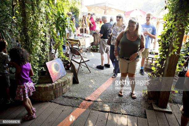 Visitors walk near a painted line indicating the anticipated center line for the upcoming total solar eclipse in Makanda Illinois US on Saturday Aug...