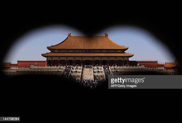 Visitors walk near The Hall of Supreme Harmony inside the Forbidden City in Beijing on April 12 2012 Located in the middle of Beijing the Forbidden...
