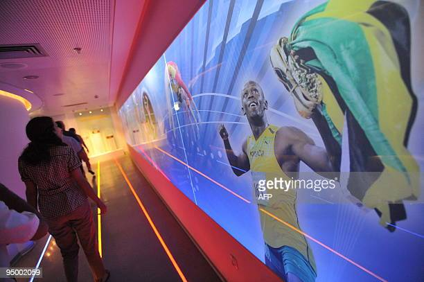 Visitors walk next to a picture of Jamaican athlete Usain Bolt from the last the Beijing 2008 Olympic Games at the newly opened Olympic museum in Tel...