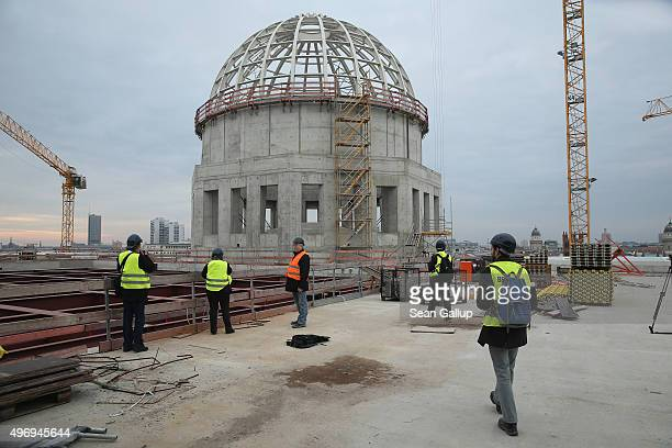 Visitors walk next to the cupola on a terrace during a media day at the construction site of the Berliner Schloss city palace on November 13 2015 in...
