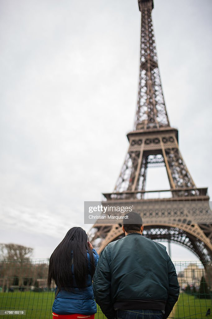 Visitors walk next to the Eiffel Tower during a grey day on March 2, 2014 in Paris, France. The Tower is located on the Champ de Paris and is a global culture icon of France.