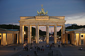 Visitors walk on Pariser Platz square in front of the illuminated Brandenburg Gate at twlight on May 19 2015 in Berlin Germany Berlin is among...