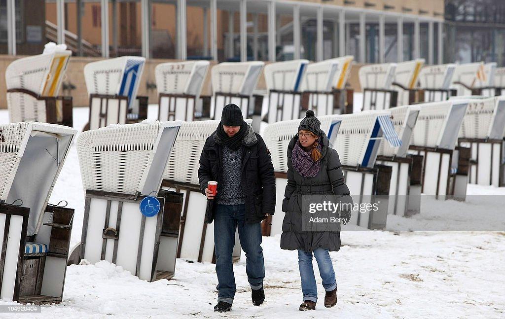 Visitors walk on the snow-covered Strandbad Wannsee beach during its opening for the year on March 29, 2013 in Berlin, Germany. Despite continued unseasonably cold temperatures in the country, organizers opened the beach for bathers in time for the last weekend of March, when Easter Sunday is expected to be colder than the previous Christmas Day had been.
