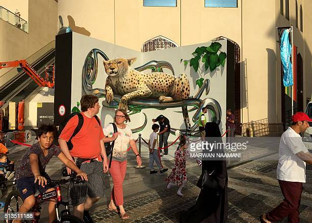 Visitors walk past a 3D artwork on March 3 2016 near the Jumeirah Beach Residence in Dubai during the Canvas Festival a threedimensional pavement art...