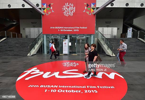 Visitors walk past a banner for the Busan International Film Festival at the Busan Cinema Center in Busan on October 1 2015 Stars from Asia and...