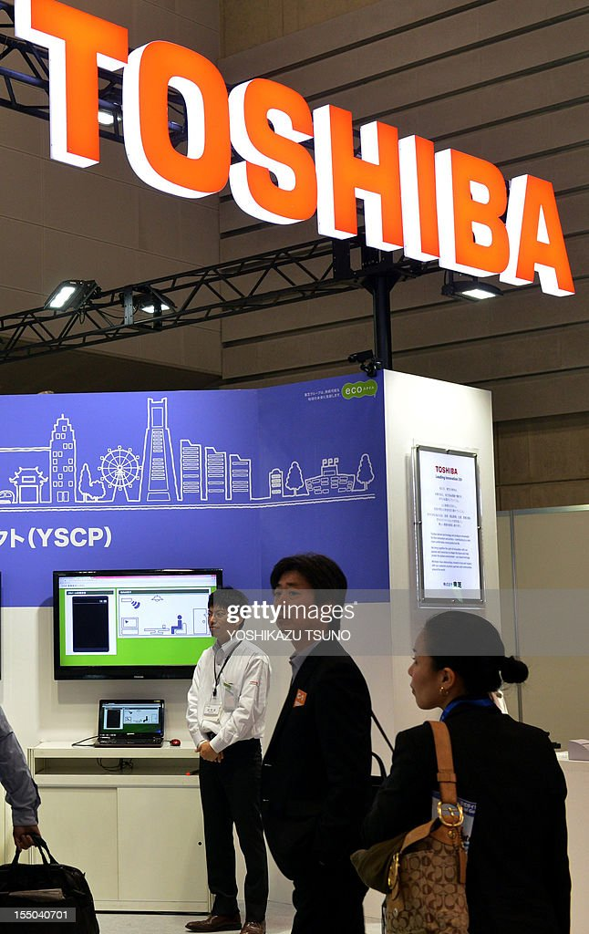 Visitors walk past a booth for a smart city project by Japan's electronics giant Toshiba at an exhibition in Yokohama, suburban Tokyo on October 31, 2012. The TV and laptop computer maker on October 31 cut its net profit outlook to 110 billion yen (1.38 billion USD) from 135 billion yen for the year to March. AFP PHOTO / Yoshikazu TSUNO