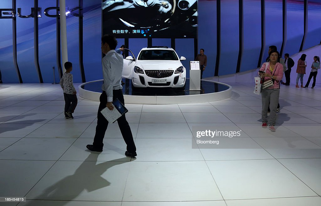 Visitors walk past a Buick Regal GS vehicle displayed at the Shanghai General Motors Co. booth, the joint venture between General Motors Co. and SAIC Motor Corp., at the Wuhan Motor Show 2013 in Wuhan, China, on Saturday, Oct. 19, 2013. The show will be held through Oct. 23. Photographer: Tomohiro Ohsumi/Bloomberg via Getty Images