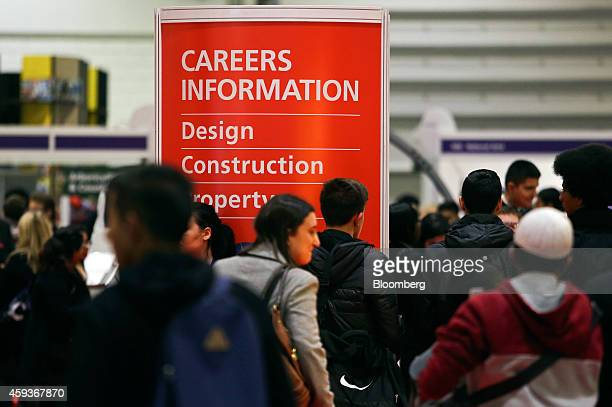 Visitors walk past a Careers Information display board as they pass job exhibition booths during the Skills London job fair in London UK on Friday...