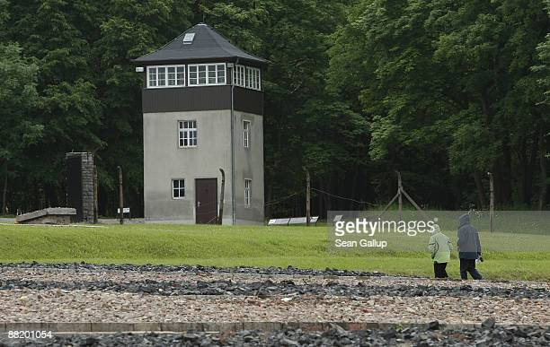 Visitors walk past a former guard tower on the grounds of the former Buchenwald concentration camp on June 4 2009 near Weimar Germany US President...